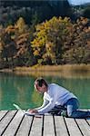 Man Sitting on Dock, Using Laptop, Fuschlee, Fuschl am See, Salzkammergut, Salzburger Land, Austria    Stock Photo - Premium Rights-Managed, Artist: Bettina Salomon, Code: 700-02428744