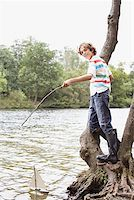 Boy playing with toy sailboat in lake Stock Photo - Premium Royalty-Freenull, Code: 635-02614248