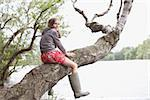 Girl climbing tree near lake Stock Photo - Premium Royalty-Freenull, Code: 635-02614296
