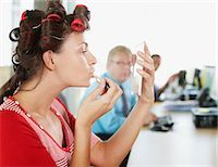 Businesswoman in curlers applying lipstick at desk Stock Photo - Premium Royalty-Freenull, Code: 635-02614448