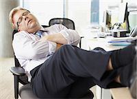 Businessman sleeping with feet up at desk Stock Photo - Premium Royalty-Freenull, Code: 635-02614504