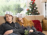 Sleeping couple wearing paper crowns at Christmas Stock Photo - Premium Royalty-Freenull, Code: 635-02614671