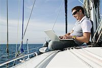 A man using a laptop on a yacht Stock Photo - Premium Royalty-Freenull, Code: 653-02635021