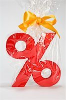 percentage symbol - Percentage sign wrapped in plastic and tied with a bow Stock Photo - Premium Royalty-Freenull, Code: 653-02635153