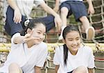 Elementary students sitting on play equipment Stock Photo - Premium Royalty-Freenull, Code: 670-02642765