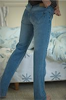 Woman putting on snug-fitting jeans, cropped view Stock Photo - Premium Royalty-Freenull, Code: 632-02645061
