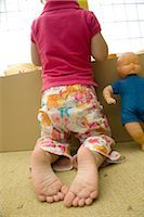 Little girl kneeling before box of toys, rear view Stock Photo - Premium Royalty-Freenull, Code: 632-02645119