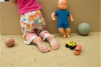 Little girl kneeling on floor with toys, rear view, cropped Stock Photo - Premium Royalty-Freenull, Code: 632-02645139