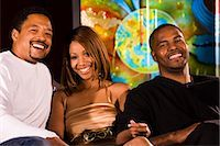 Portrait of three young African American people sitting at nightclub, low angle view    Stock Photo - Premium Rights-Managednull, Code: 842-02652470
