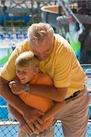 Father and son hugging and wrestling with water park in background    Stock Photo - Premium Rights-Managednull, Code: 842-02653911