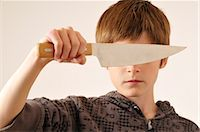 Boy Holding Knife in Front of Eyes    Stock Photo - Premium Royalty-Freenull, Code: 600-02670199