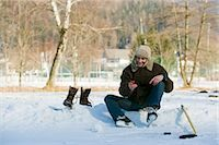 Man Sitting by Ice Rink Looking at Cell Phone, Fuschl am See, Salzburg, Austria    Stock Photo - Premium Rights-Managednull, Code: 700-02670590