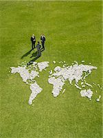 Businesspeople meeting near world map made of rocks Stock Photo - Premium Royalty-Freenull, Code: 635-02681722