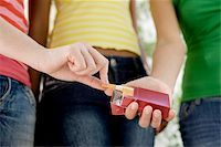 Underage smoking. Young teenage girl taking a cigarette from her friend's packet. Stock Photo - Premium Royalty-Freenull, Code: 679-02682485