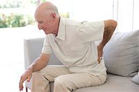 Lower back pain. Man rubbing his aching back. Stock Photo - Premium Royalty-Freenull, Code: 679-02682668