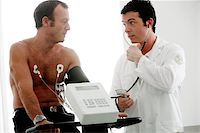 Heart fitness test. Doctor using a stethoscope and arm cuff to measure a patient's blood pressure. The patient has just ridden an exercise bike during an assessment of his cardiovascular system. He is fitted with electrodes (round), which monitor the electrical activity of his beating heart. This test is used to diagnose arrhythmia (irregular heartbeat), and some forms of coronary artery disease./ Stock Photo - Premium Royalty-Freenull, Code: 679-02684443