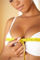 Breast size. Woman measuring her breast size (bust size) with a tape measure. The bust size, measured over the fullest part of the breasts, is a measurement used to determine the size of clothes to wear, such as blouses and shirts. The bra size is determined by two other measurements, the underbust size (chest size under the breasts) and the cup size (fullness of the breasts). Stock Photo - Premium Royalty-Freenull, Code: 679-02685448