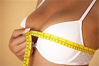 Breast size. Woman measuring her breast size (bust size) with a tape measure. The bust size, measured over the fullest part of the breasts, is a measurement used to determine the size of clothes to wear, such as blouses and shirts. The bra size is determined by two other measurements, the underbust size (chest size under the breasts) and the cup size (fullness of the breasts). Stock Photo - Premium Royalty-Freenull, Code: 679-02685449