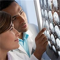 Doctors examining MRI scans. The scans are sagittal (side view) sections through a patient's head. MRI is an important diagnostic tool that allows imaging of internal structures. It uses a powerful magnet and radio waves to image the body, and is particularly useful for imaging the brain. Stock Photo - Premium Royalty-Freenull, Code: 679-02685495