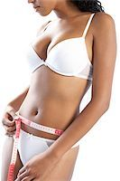 Waist size. Woman in her underwear, measuring her waist size using a tape measure. Her waist size is 80 centimetres (31.5 inches). Stock Photo - Premium Royalty-Freenull, Code: 679-02685563