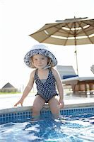 Girl Wearing Bathing Suit and Sunhat, sitting on Edge of Swimming Pool, Cancun, Mexico    Stock Photo - Premium Royalty-Freenull, Code: 600-02686151