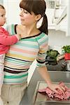 Woman Holding Baby While She Cleans Kitchen    Stock Photo - Premium Rights-Managed, Artist: Klick, Code: 700-02686105