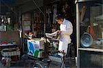 Shopkeeper Reading Newspaper, Zhenjiang, Jiangsu, China    Stock Photo - Premium Rights-Managed, Artist: Mark Downey, Code: 700-02700785