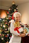 Portrait of Woman Holding Christmas Gifts in front of Christmas Tree    Stock Photo - Premium Rights-Managed, Artist: Raoul Minsart, Code: 700-02702517