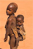 Young Hamer girl carries her baby sister on her back in a goat skin baby carrier, Dombo village, Turmi, Lower Omo valley, Ethiopia, Africa    Stock Photo - Premium Rights-Managednull, Code: 841-02707359