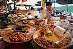 A shopkeeper puts fish cakes on a tray on a stall in the Weekend market in Bangkok, Thailand, Southeast Asia, Asia