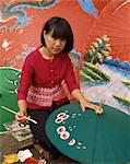 Portrait of a woman hand painting umbrellas in Chiang Mai, Thailand, Southeast Asia, Asia