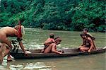 Yanomami crossing river in boat, Brazil, South America