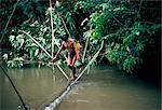 Yanomami man carrying peach palm fruit crossing a river, Brazil, South America
