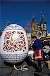 A Moravian woman decorating a large egg with Easter designs on the Old Town Square, with Tyn Church in the background, Prague, Czech Republic, Europe