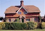 Tile - hung cottage with central chimney, bargeboards and porch. Patterned roof tiles. Rural. Stedham, Sussex. C.1900    Stock Photo - Premium Rights-Managed, Artist: Arcaid, Code: 845-02729349