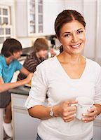Mother in Kitchen With Cup of Coffee, Sons Eating Breakfast in the Background    Stock Photo - Premium Rights-Managednull, Code: 700-02738788