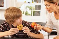 Mother Trying to Get Son to Eat an Apple Instead of a Cookie    Stock Photo - Premium Rights-Managednull, Code: 700-02738797