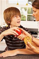 Mother Trying to Get Son to Eat an Apple Instead of a Cookie    Stock Photo - Premium Rights-Managednull, Code: 700-02738798