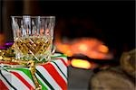 Close up of a glass of whiskey on a gift box  in front of a log fire    Stock Photo - Premium Rights-Managed, Artist: ableimages, Code: 822-02738937