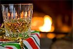 Close up of a glass of whiskey on a gift box  in front of a log fire    Stock Photo - Premium Rights-Managed, Artist: ableimages, Code: 822-02738938