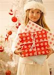 Close up of a girl standing by a Christmas tree holding gifts    Stock Photo - Premium Rights-Managed, Artist: ableimages, Code: 822-02739127