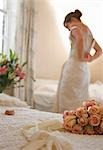 Close up of a bouquet of roses and bridal gloves lying on a bed with bride undressing    Stock Photo - Premium Rights-Managed, Artist: ableimages, Code: 822-02739130