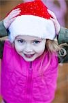 Close up of a girl wearing a red and white Chistmas hat with her hands on her head    Stock Photo - Premium Rights-Managed, Artist: ableimages, Code: 822-02739196