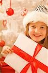 Close up of a smiling girl in a furry hat holding Christmas gift    Stock Photo - Premium Rights-Managed, Artist: ableimages, Code: 822-02739208
