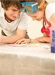 Close up of a smiling couple leaning over a table face to face looking at paint colour swatches