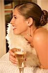 Profile of a woman wrapped in a swan feather stole holding a glass of champagne - close up    Stock Photo - Premium Rights-Managed, Artist: ableimages, Code: 822-02739372