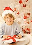 Boy sitting by Christmas tree in a red and white furry hat unwrapping a gift    Stock Photo - Premium Rights-Managed, Artist: ableimages, Code: 822-02739433