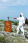 Person in protective suit placing dead fish in hazardous waste barrel Stock Photo - Premium Royalty-Free, Artist: Ikon Images, Code: 632-02745055