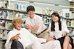 Portrait of three high school students messing about in library