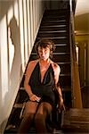 Portrait of sexy hooker sitting on stairs in house